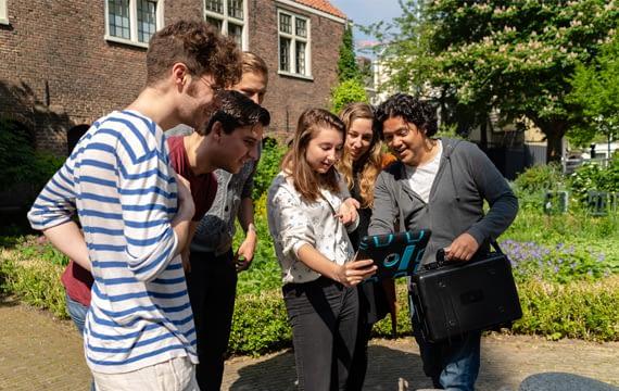Een groep deelnemers bespreekt een opdracht op de iPad